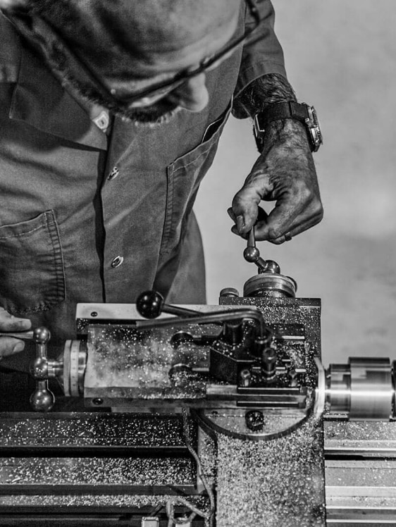 A man uses a lathe to turn and machine the inside of a watch case.