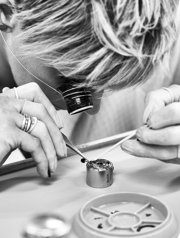 A watchmaker looking through an eyepiece as she works on a watch